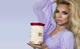 在拿着玫瑰的花束庄重装束的美好的白肤金发的模型,花箱子 华伦泰的和生日礼物在蓝色背景 库存图片