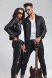 在拿着电吉他的皮夹克的性感的夫妇 免版税库存照片