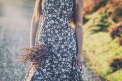 在拿着石南花花的花束夏天礼服的女性模型 库存照片