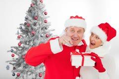 在拿着礼物盒的圣诞老人帽子的夫妇在圣诞树附近 免版税图库摄影