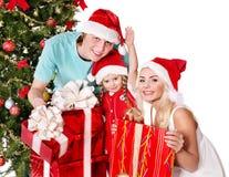 在拿着礼物盒的圣诞老人帽子的愉快的家庭。 库存照片