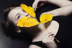 在拿着秋天叶子的地板上的女孩 库存照片