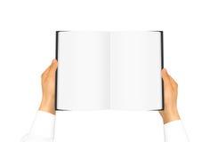 在拿着空白的书的白色衬衣袖子的手 图库摄影
