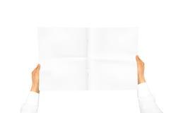 在拿着空白的学报的白色衬衣袖子的手 免版税库存图片