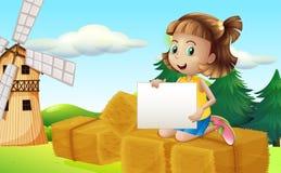 在拿着空的标志的干草上的一个女孩 图库摄影