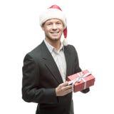 在拿着红色礼物的圣诞老人帽子的快乐的商人 免版税库存图片