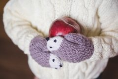 在拿着红色苹果的舒适手套的孩子手 免版税库存图片