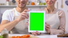 在拿着绿色屏幕片剂的围裙的快乐的夫妇坐在厨房收据 影视素材
