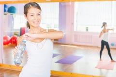 在拿着自然水的健身锻炼以后的愉快的亚裔妇女 免版税库存图片