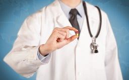 医治在拿着药片的白色 库存照片