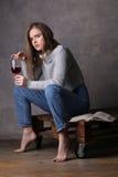 在拿着葡萄酒杯的套头衫的模型 灰色背景 免版税库存照片