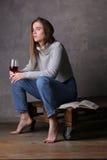 在拿着葡萄酒杯的毛线衣和牛仔裤的模型 灰色背景 库存照片