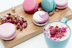在拿着蓝色杯子与玫瑰花瓣的热奶咖啡的书桌和手上的秀丽法国macarons在白色背景桌上 免版税图库摄影