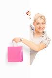 在拿着袋子的空白面板之后的微笑的女性 免版税库存图片