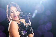 在拿着话筒的音乐会期间的美丽的妇女 免版税库存图片