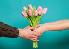 在拿着郁金香的花束在蓝色背景的爱的夫妇。 库存图片