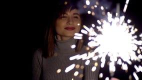 在拿着闪烁发光物和庆祝圣诞节和享受光的秀丽的女孩的面孔的微笑 股票视频