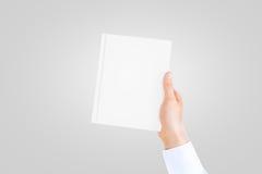 在拿着闭合的空白的书的白色衬衣袖子的手 免版税库存图片