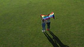 在拿着lgbt旗子的快乐夫妇的寄生虫飞行 股票录像