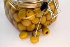 在持有人刺穿的橄榄在瓶子橄榄旁边 免版税库存照片