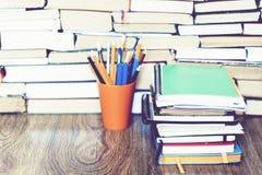 在持有人的色的铅笔与堆在书教育概念背景的笔记本 免版税库存照片