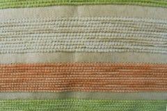 在挂毯的橙色绿色米黄条纹 织品纹理 库存图片