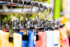 在挂衣架的丝绸围巾在零售精品店购物 图库摄影