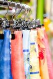 在挂衣架的丝绸围巾在零售精品店购物 库存图片