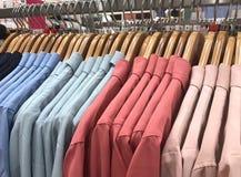 在挂衣架的五颜六色的妇女衬衣在购物商店,地球口气c 库存图片