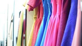 在挂衣架的五颜六色的美丽的礼服和均匀地斟酌混乱 股票录像