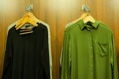 在挂衣架的人的衣物在时尚商店 绿色衬衣和黑套头衫 木背景 购物和折扣的概念 免版税库存图片