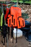 在挂衣架的橙色和黄色救生衣 免版税库存照片