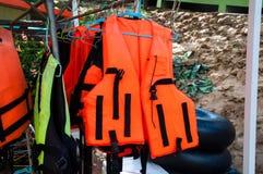 在挂衣架的橙色和黄色救生衣 库存图片