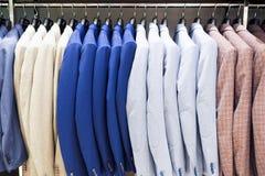 在挂衣架的男性夹克在商店 图库摄影