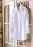 在挂衣架的白色棉布衬衣 免版税库存照片