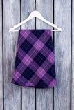 在挂衣架的紫色方格的裙子 库存照片