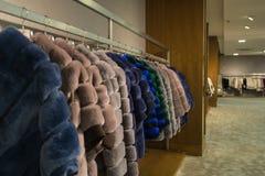 在挂衣架的花梢外套在商店 免版税图库摄影