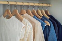 在挂衣架的衣裳在从白色的内阁梯度到黑暗的bl 库存照片