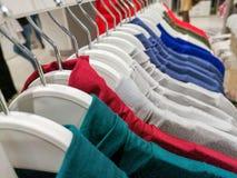 在挂衣架的衣裳在商店 衣裳在一个架子垂悬在不同颜色的一家设计师服装商店 免版税库存照片