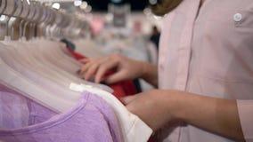 在挂衣架的顾客女性精选的新的时髦的衣物在销售折扣,在未聚焦的手期间的时尚商店 股票视频