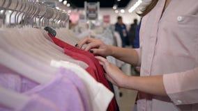 在挂衣架的Shopaholics妇女精选的新的时装在销售折扣,在未聚焦的背景的手期间的商店 影视素材