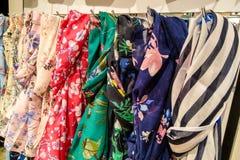 在挂衣架,背景的美丽的多彩多姿的围巾 库存照片