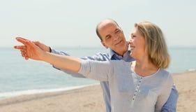 在指向手指的便衣的愉快的夫妇 免版税图库摄影