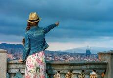 在指向某事的巴塞罗那前面都市风景的妇女 库存照片