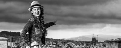 在指向某事的巴塞罗那前面都市风景的妇女 免版税库存照片