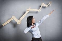 在指向的激动的女实业家企业图前面 免版税库存图片