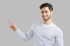 在指向空白年轻人的背景英俊的查出的人 免版税库存照片