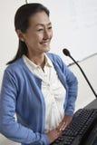 在指挥台前面的女性教授Standing 免版税图库摄影