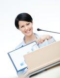 在指挥台的兴高采烈的女性报告人 免版税库存图片