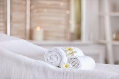 在按摩桌上的毛巾在现代温泉沙龙 安置放松 免版税库存图片